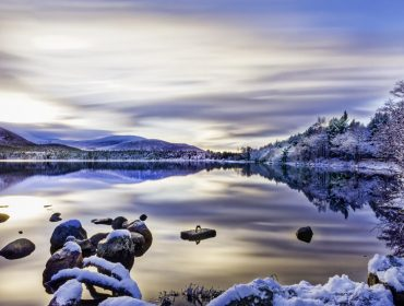Beautiful winters day with soft clouds, snow on trees and rocks, reflections on calm water at Loch Morlich, Aviemore