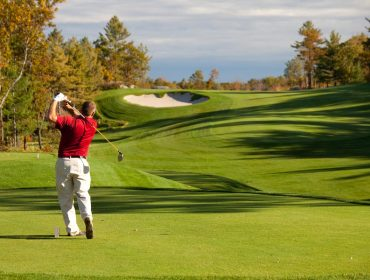 A landscape photo of a golf player wearing a red shirt and tan trousers tees off with the fairway and sandbox in the background