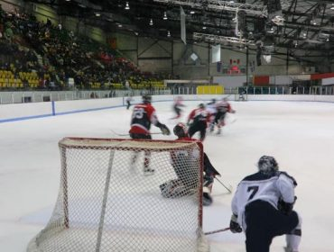 A photo from behind the goalie showing blurred players moving on the ice