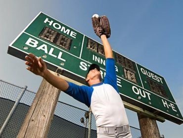 A portrait photo of a baseball player catches the ball under the scoreboard