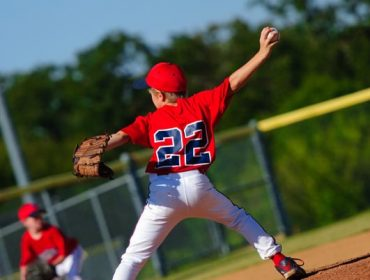 A portrait photo of a young baseball player pitches the ball