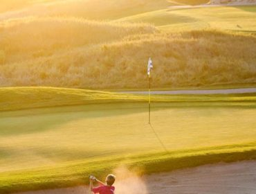 A portrait photo of a young golf player wearing a red shit and tan shorts trying to get out of the sandbox and onto the green with the sun setting in the background