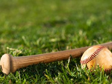 A landscape photo of a baseball bat's grip end with a baseball in front of it lying on grass