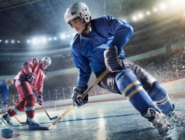 A landscape photo of three ice hockey players, two in blue and one in red