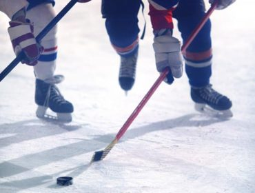 A portrait photo of two ice hockey players, one in white and the other in red, battling for the puck