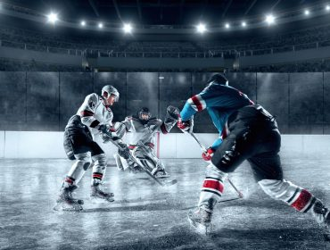 A landscape photo of three ice hockey players, two in black and white, and one in blue, red and white