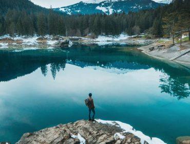 Young Caucasian man walking near Cauma lake in Switzerland in winter